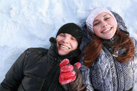 Pair of lovers people lies on snow hold on hands and laugh photo