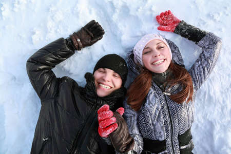 Two lovers people lie on in winter on snow  holding  hands and smile photo