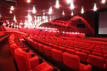 Rows of comfortable red chairs in illuminate red room cinema Stock Photo - 12512780