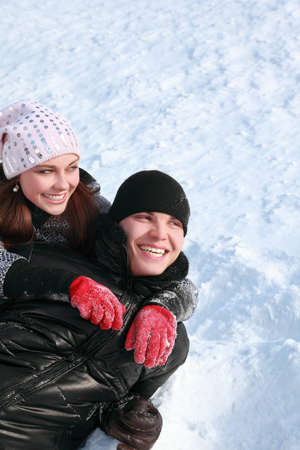 Young people lie sideways on snow, laugh and look aside photo