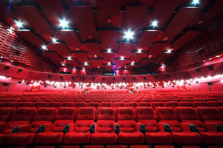 Low-angle view of ceiling and rows of comfortable red chairs in illuminate red room cinema