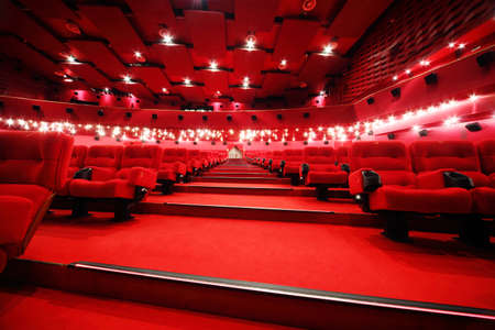 empty stage: Low-angle view of stairs between rows of comfortable red chairs in illuminate red room cinema Editorial