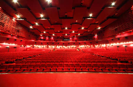 showtime: View from stage on ceiling and rows of comfortable red chairs in illuminate red room cinema Editorial