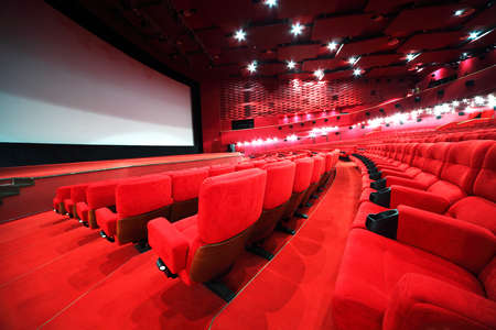 red chair: View from stairs on rows of comfortable red chairs in illuminate red room cinema