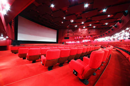 View from stairs on screen and rows of comfortable red chairs in illuminate red room cinema Editorial