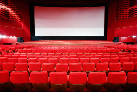View on screen through rows of comfortable red chairs in illuminate red room cinema