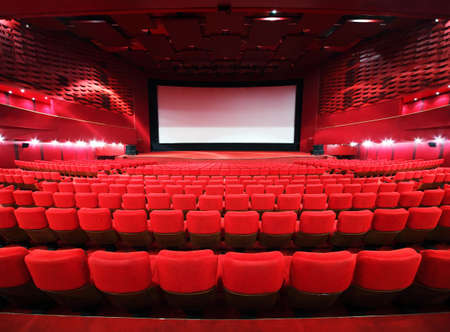 Rows of comfortable red chairs towards to big screen in illuminate red room cinema  Editorial