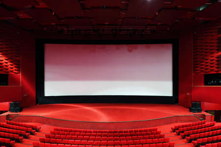High-angle view of screen and rows of comfortable red chairs in illuminate red room cinema photo