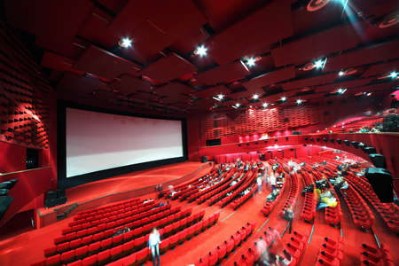 High-angle view of screen and rows of comfortable red chairs filled by people in illuminate red room cinema