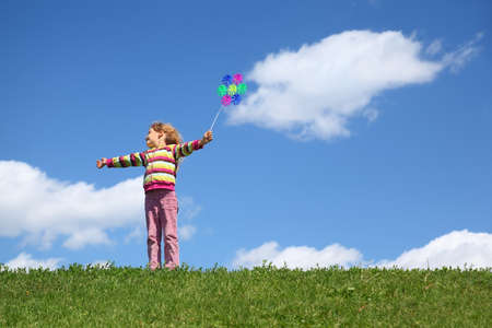 molino: Chica se encuentra en la hierba en verano se ve a un lado y tiene molino de viento en la mano Foto de archivo