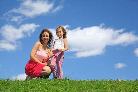 en cuclillas: Madre en cuclillas junto con la hija que tiene para la mano y se ríe