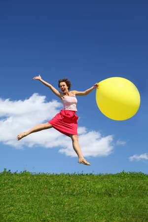 rebound: Woman in summer pushes off from earth and on wing holds  yellow inflatable ball Stock Photo