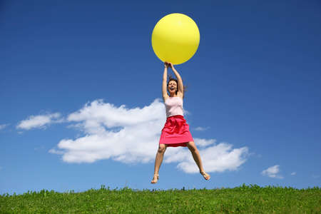 descend: Woman by canicular day descend on inflatable ball on grass