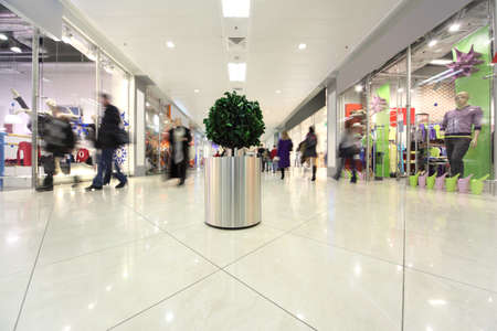 market hall: white corridor in shopping mall, potted tree and people in motion Editorial