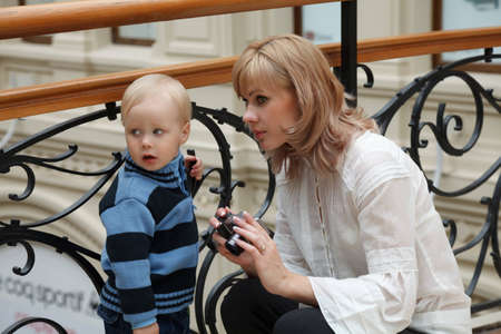 Beautiful woman and its little boy indoors against forged fencing, with camera in hands look aside. Stock Photo - 12734300