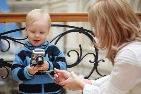 Child and mother. Boy examines photo with digital camera.
