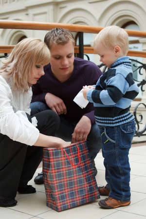 Family from three persons, husband with wife and their small son, looking at package, walks on shops.