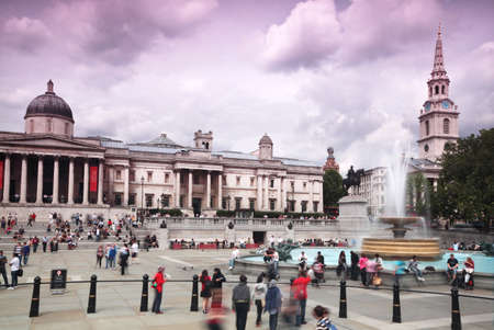 People stand at fountain at Trafalgar Square in front of the National Gallery in London.
