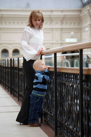 banister: Little boy near to mum costs at fencing and having put hands on handrail looks in distance.