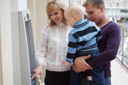 Jonge familie met kind ontvangt geld van contant geld af te geven. Vader houdt zoon op handen. Stockfoto