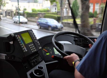 bus driver: el hombre en camisa azul en un autob�s en una carretera mojada en un d�a lluvioso, nublado