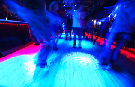Legs of energy dancing people on the dance floor at night club