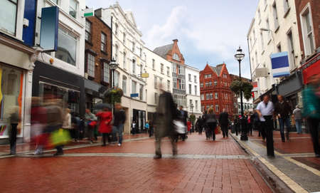 dublin ireland: people quickly going on small, narrow street in cloudy weather