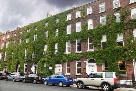 several cars parked near the four-storey building of red brick with ivy