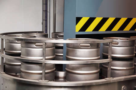 several aluminum beer barrels move on the conveyor. blue wall is located behind the conveyor Stock Photo - 12512749