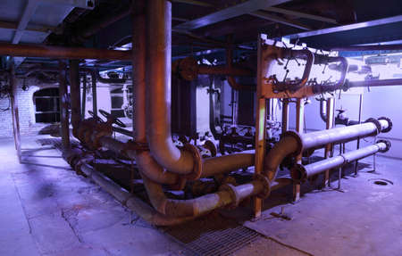 a lot of old pipes with valves located in a dirty basement