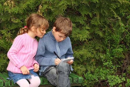 little boy and girl sitting on bench near trees, boy writing in notebook, girl looking on it photo