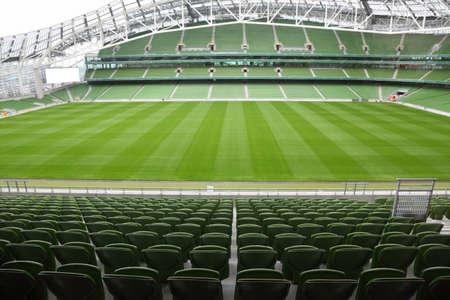 stadium: Rows of green seats in an empty stadium. Focus on front seats