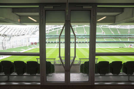grandstand: Door and rows of green, folding seats in a big empty stadium.