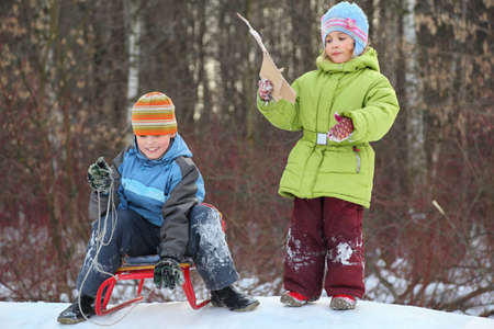 Brother and sister intend  drive from  hill in winter on sledges photo