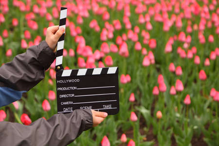 Cinema clapper board in hands of boy on field with tulips photo