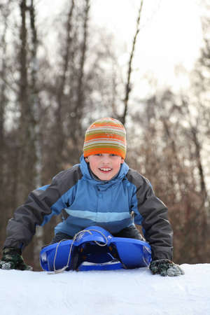 fascination: Boy intend  drive from  hill in winter on sledges and push off hands