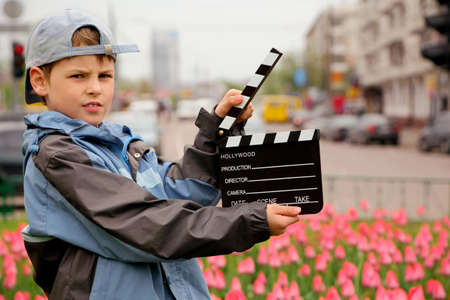 A boy in jacket and cap with cinema clapper board in hands standing on field with tulips on of urban streets
