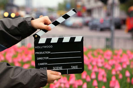 Cinema clapper board in the hands of boy on field with tulips on urban streets photo