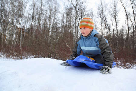 fascination: Boy by push off  intend  drive from  hill in winter on sledges Stock Photo