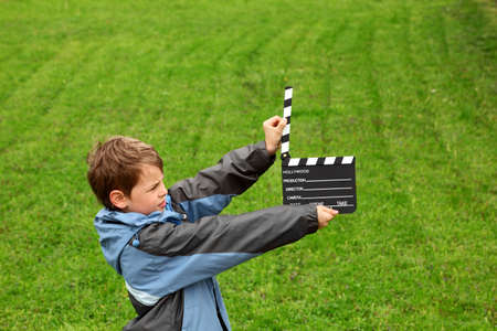 boy in jacket with cinema clapper board in their hands standing on field with green grass