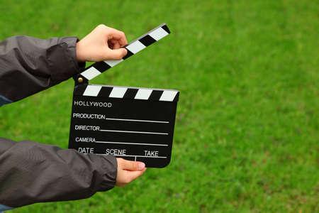 clapper board: Cinema clapper board in hands of boy in jacket on field with green grass Stock Photo