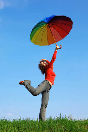 aloft: girl standing on one leg on green grass with colorful umbrellas aloft in hand against blue sky