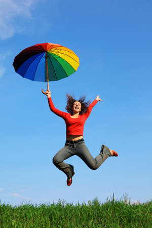 girl jumping over green grass with colorful umbrella in hand against blue sky Stock Photo