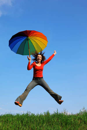 girl jumping over green grass with colorful umbrella in hand against blue sky photo