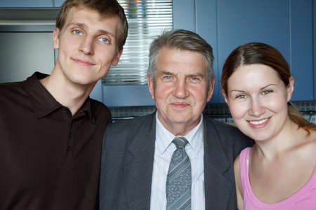 Family of three people. Man, old man and girl smiling looking at camera. photo