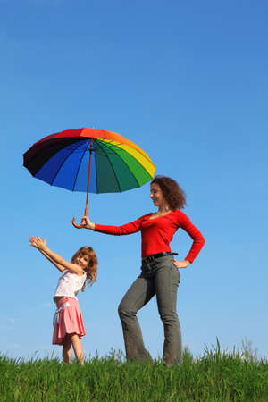 Mother stands on field with green grass against blue sky and holding colorful umbrella over her daughter, who is standing next to her