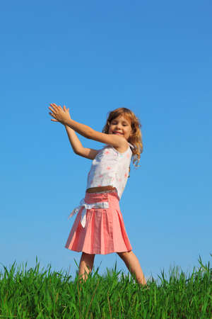 grass skirt: Joyful girl stands in field with green grass against blue sky, raising his hands up Stock Photo
