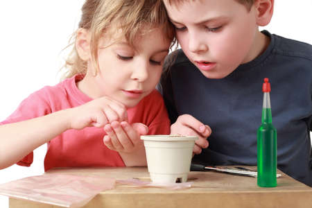 fascination: Girl shows  brother how to sow grains in  pot
