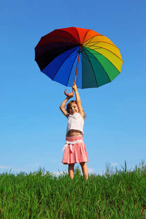 aloft: smiling girl stands on green grass on blue sky background with colored umbrella aloft over his head in his hands Stock Photo