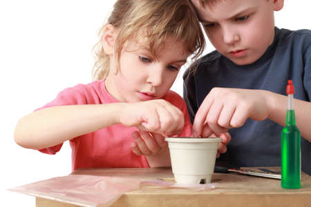 Girl and boy seat grains in  pot